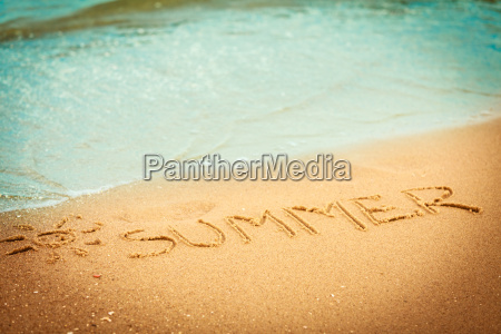 ordet sommer skrevet i sandet pa