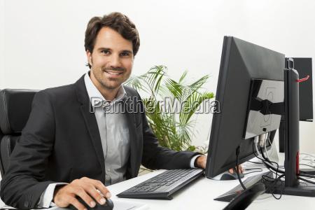 unge succesrig forretningsmand med sort jakkesaet
