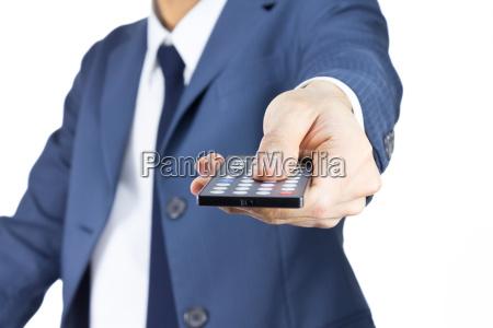 forretningsmand med fjernbetjening isoleret pa hvid