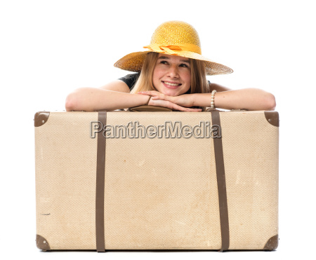young girl sitting behind a suitcase
