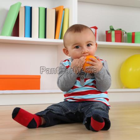 little baby spiser en appelsin frugt