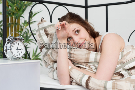 young woman lies awake in bed