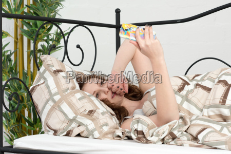 young woman lying with cell phone