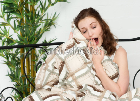 young woman cuddles with the bedspread