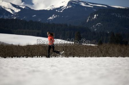 ung kvinde lober gennem sneen med
