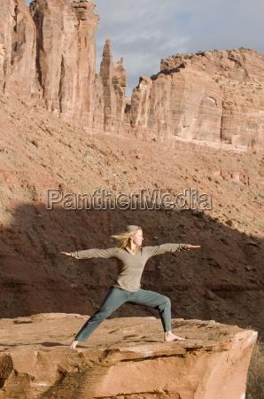 kvinde i yogastilling pa sandsten klippe