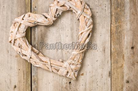 flettet hjerte foran rustikke traebraedder