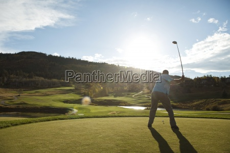 en golfspiller korer ved solnedgang i
