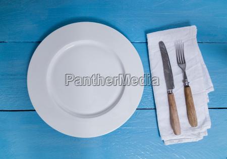bestik og tallerkener pa en bla
