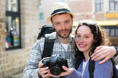 young couple of tourist watching photographs