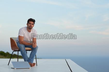 afslappet ung mand hjemme pa altanen