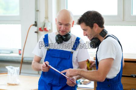 chef og arbejdstager i et snedkervaerksted