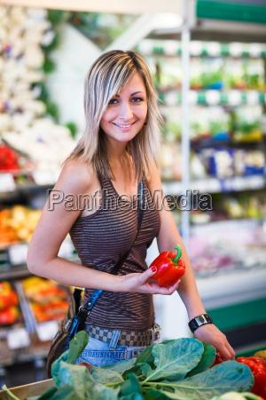 smuk ung kvinde shopping for frugt