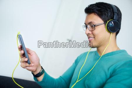 kinesisk mand med gronne hovedtelefoner lytter