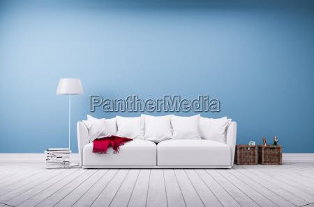 sofa og standerlampe mod bla betonvaeg