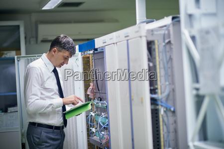 netvaerkstekniker der arbejder i serverrum
