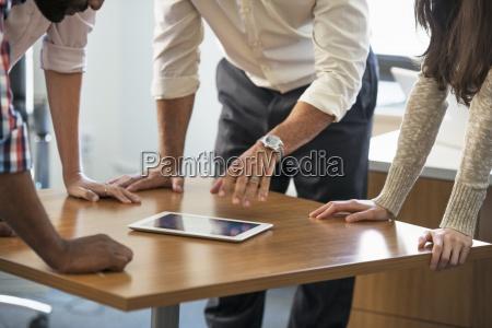 fire mennesker haelder pa et bord