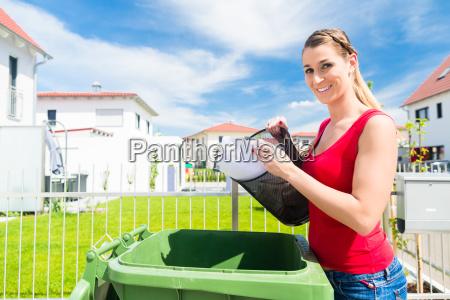 kvinden bringer ud med skraldespanden i