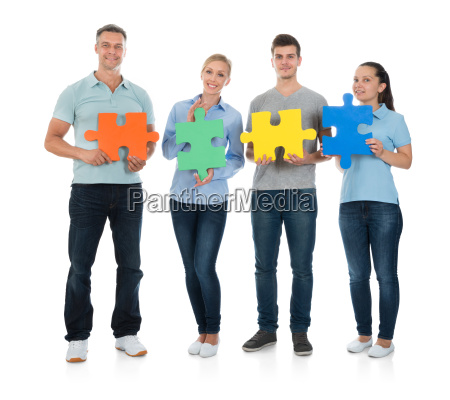 happy people holding jigsaw pieces
