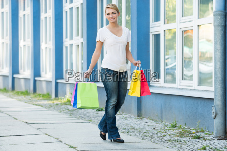 woman carrying shopping bags on sidewalk