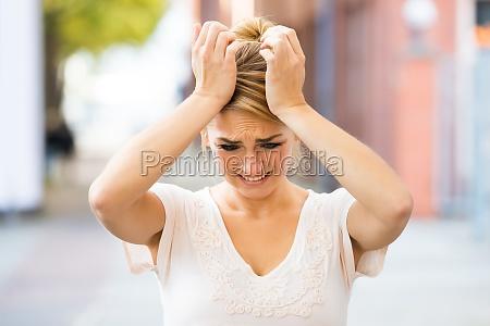 kvinde der lider af hovedpine udendors