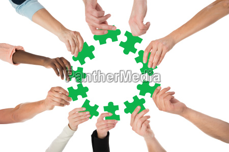 creative business people holding green jigsaw