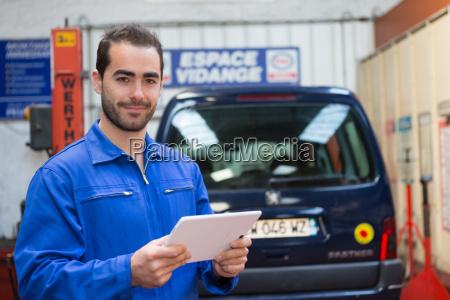 unge attraktive mekaniker arbejder pa garage