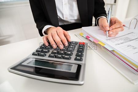 forretningskvinde gor okonomisk beregning ved skranken