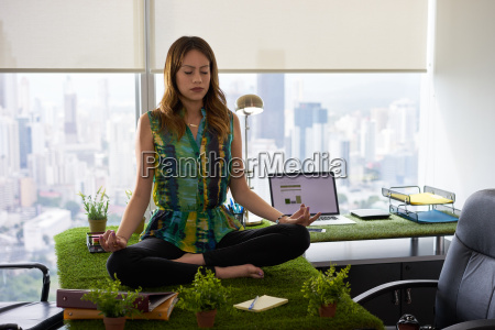 forretning kvinde laver yoga meditation pa