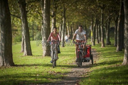 family riding bicycle in park