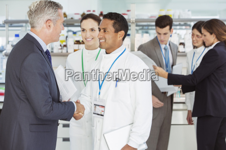 scientist and businessman shaking hands in