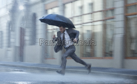 businessman with umbrella running across rainy