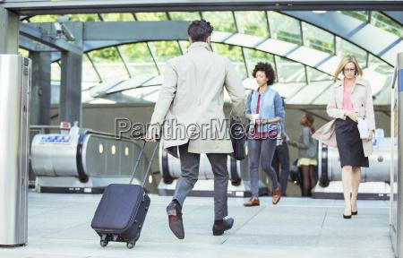 businessman pulling luggage near escalators