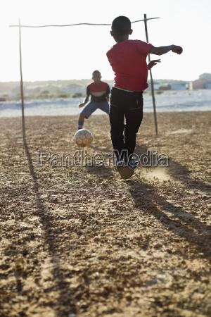 drenge spiller fodbold sammen i snavs