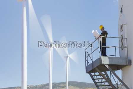 businessman examining blueprints by wind turbines