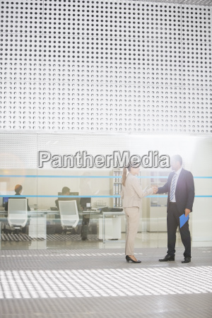 businessman and businesswoman handshaking outside office