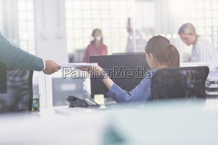 businessman handing paperwork to businesswoman at