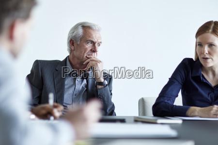 attentive senior businessman listening to businesswoman