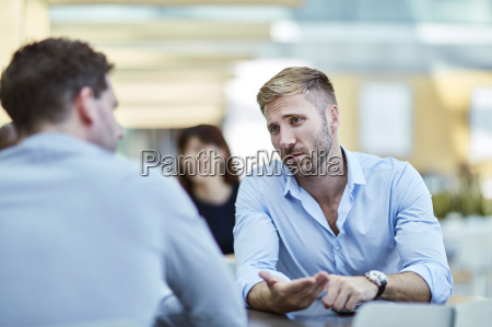 businessman gesturing and talking to colleague