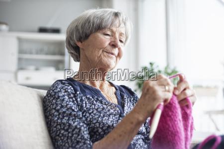 portraet af strikning senior kvinde sidder