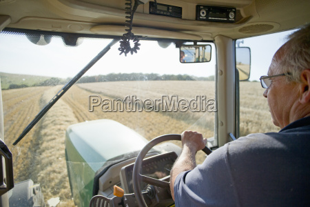 farmer at steering wheel of tractor