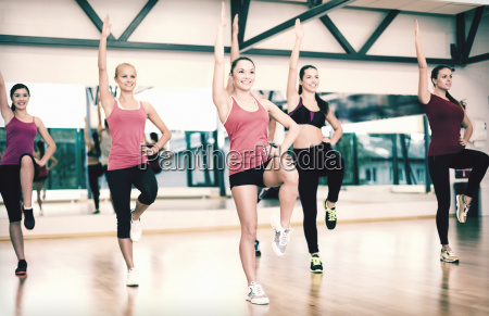 group of smiling women exercising in