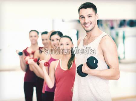 group of smiling people with dumbbells