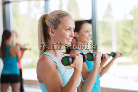 group of women exercising with dumbbells