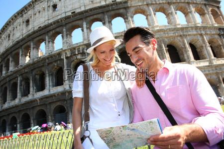 turister laeser kort foran colosseum rom
