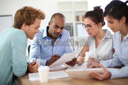 unge forretningsfolk der modes omkring bordet