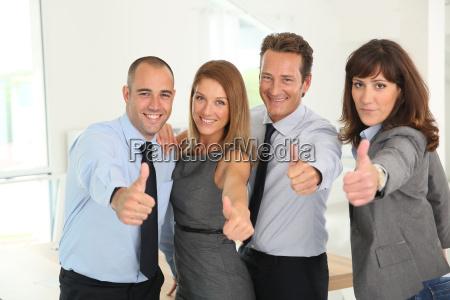 succesfuld business team viser tommelfingre op