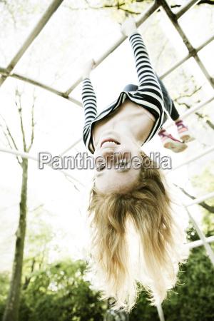 portrait of smiling girl hanging upside