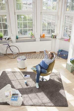 afslappet kvinde derhjemme sidder i stolen