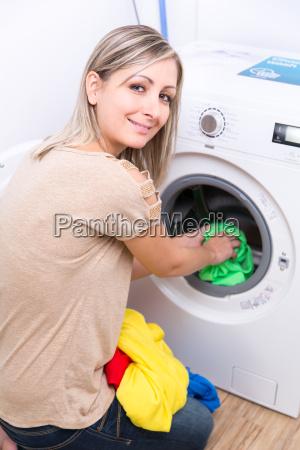 husarbejde ung kvinde laver vasketoj lavvandet